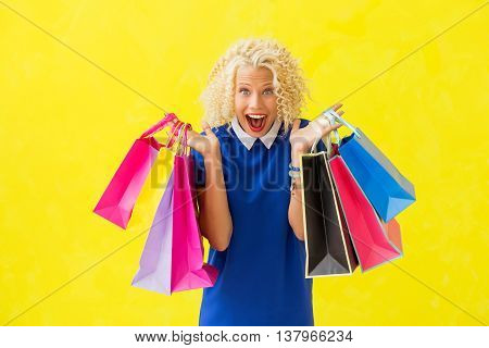 Excited woman with shopping bags in both hands