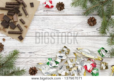 Christmas Card with chocolate candieswrappers and fir branches on white wooden background. Copy space composition.