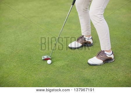 Low section of woman playing golf while standing on field