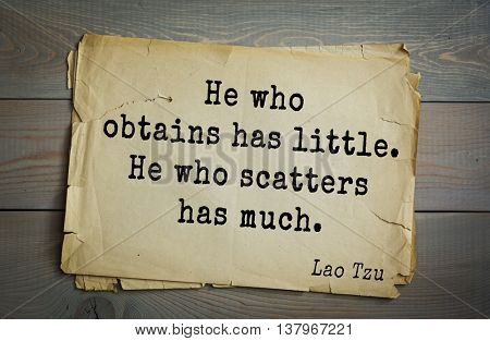 Ancient chinese philosopher Lao Tzu quote on old paper background. He who obtains has little. He who scatters has much.