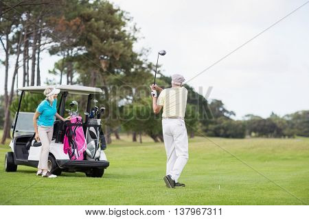 Full length of man taking shot while standing by woman at golf course