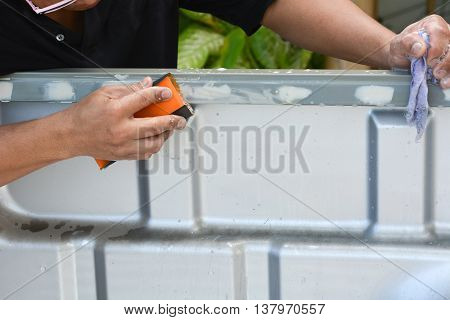 A man sanding pickup (auto body repair)