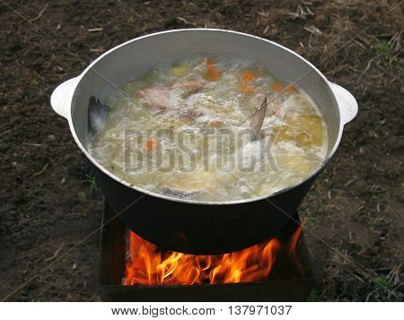 Cooking fish soup in a cauldron over the fire.