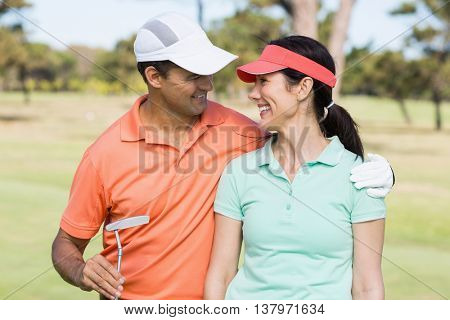 Smiling golfer couple with arm around while standing on field
