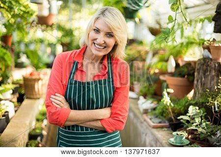 Portrait of female gardener standing amidst plants at greenhouse