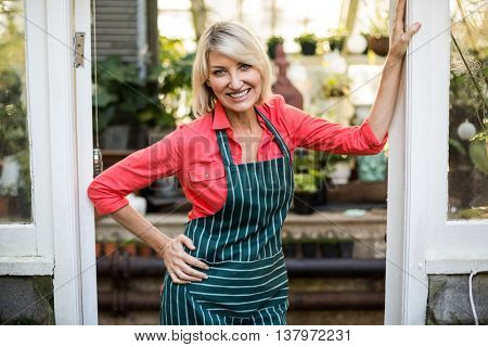 Portrait of mature woman standing at doorway in greenhouse