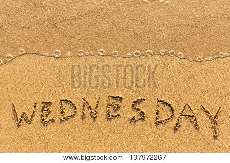 Wednesday - hand-written on the sand in line of the sea surf.