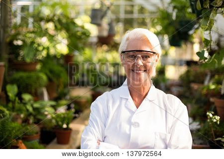 Portrait of confident female scientist wearing protective eyewear at greenhouse