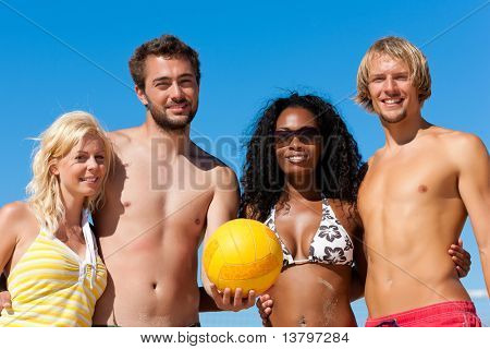Group of friends - women and men - playing beach volleyball; they having a break and lying in the sun