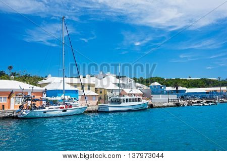 ST.GEORGE'S BERMUDA MAY 27 - Colorful buildings with white roofsturquoise colored water and boats in the harbor on May 27 2016 in St. George's Bermuda.