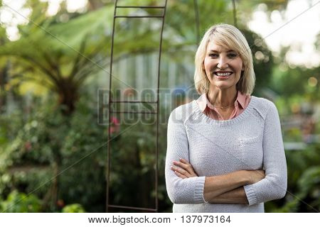 Portrait of confident woman standing at greenhouse