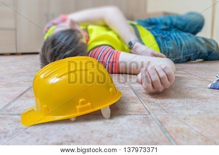 Injured Worker Had Accident. Man Is Lying On The Floor. Yellow H