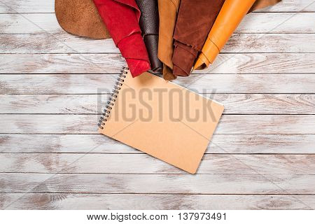Brightly colored leather in rolls and a notebook on white wooden background. Leather craft. Copy space. Top view.