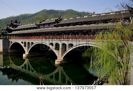 Jie Zi Ancient Town China - March 6 2013: The landmark Ruilong covered bridge with its three broad arches and decorative roofs spans a tranquil river