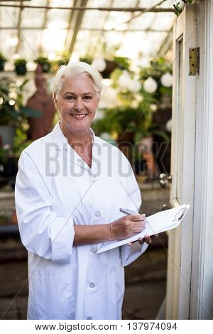 Portrait of mature female scientist with clipboard at doorway in greenhouse