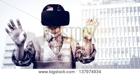 young boy in red jumper with virtual reality headset against low angle view of city buildings
