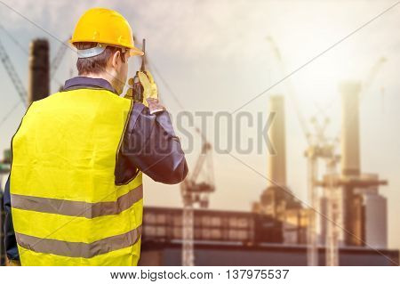 Worker Is Using Radio And Crane Site During Sunset. Construction