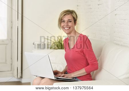young beautiful blond woman smiling happy and cheerful working at home living room with laptop computer on sofa couch satisfied and relax in domestic technology and internet concept