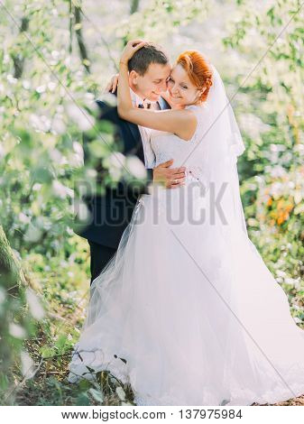 Happy young newly married couple embracing and softly smiling in the green forest.