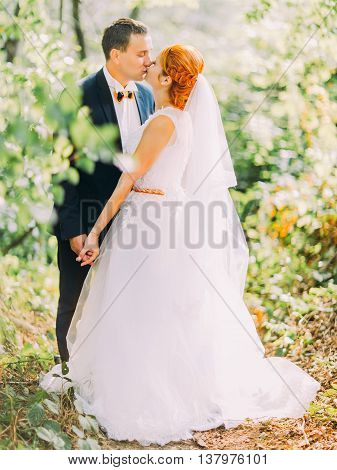 Happy young newly married couple embracing and softly kissing in the green forest.