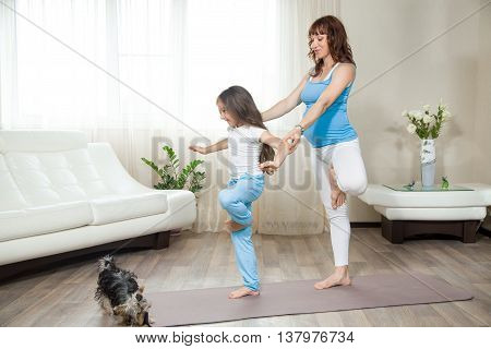 Pregnant Mother Teaching Her Kid Girl Yoga At Home