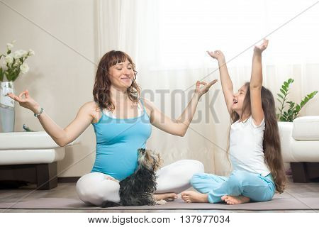 Pregnant Mother And Kid Girl Meditating At Home