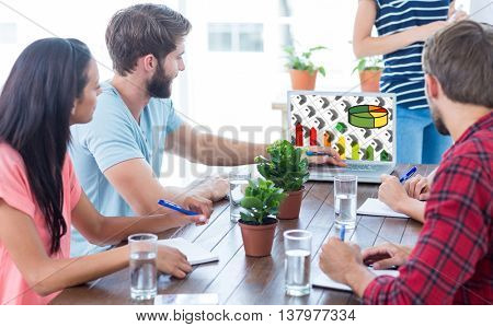 Business team using a laptop against energy efficient house graphic against a background