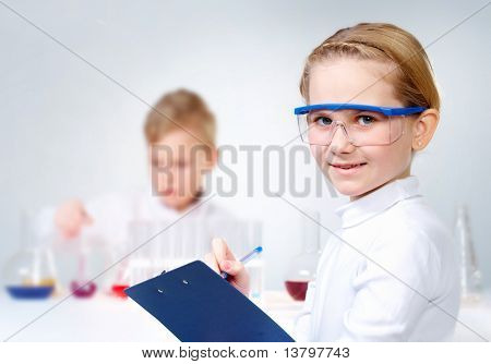 A little girl in protective glasses making notes and looking at camera