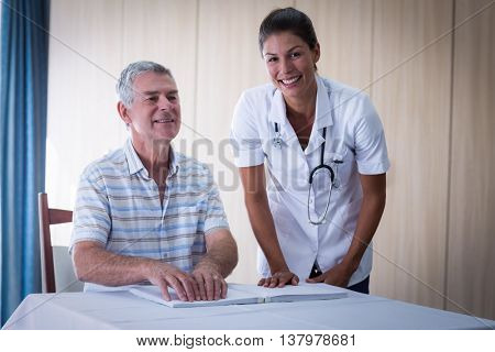 Female doctor helping patient in reading the braille book at home