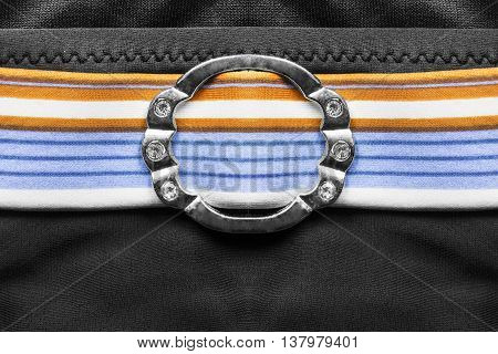 Silver buckle with crystals on striped belt closeup