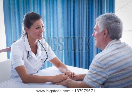 Smiling female doctor consoling senior man at home