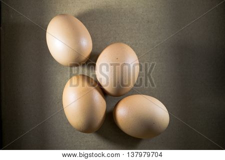 Four fresh  eggs on a brown background.