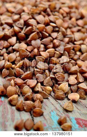 Many buckwheat groats on rustic table closeup