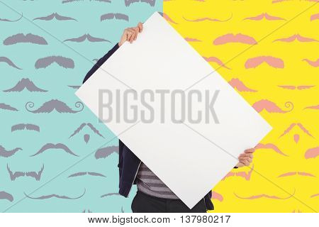 Man holding billboard in front of face against composite image of mustaches