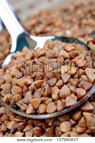 Buckwheat groats in spoon on background closeup