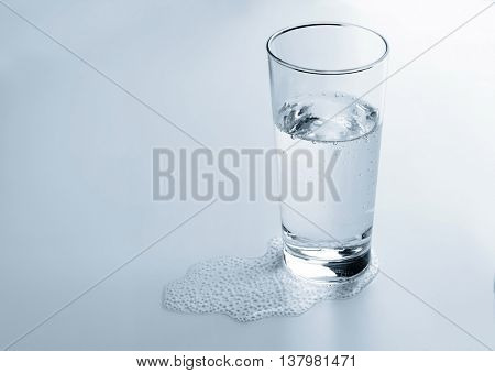 Glass and some mineral water on light background