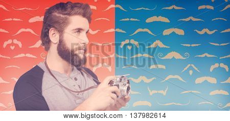Hipster using digital camera against composite image of mustaches