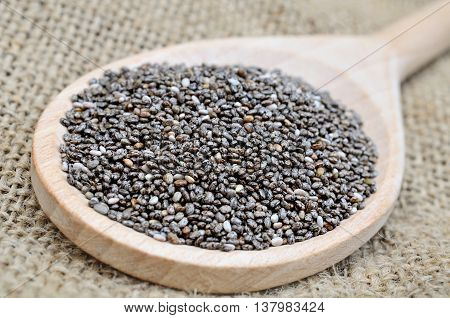 Wooden spoon with chia seeds on rustic table
