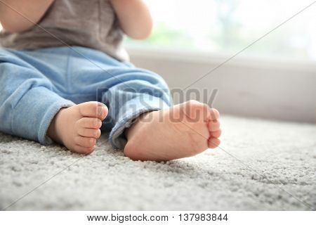 Baby boy's feet on woolen carpet, close up