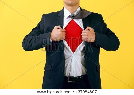 Young businessman super hero on yellow background
