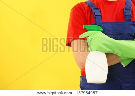 Man holding detergent on yellow background