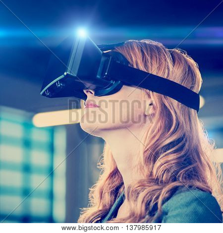 Side view of young businesswoman using virtual reality simulator in office