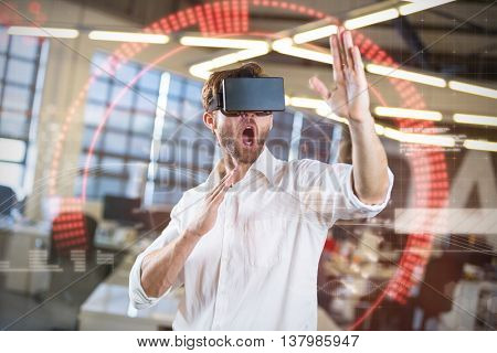 Composite image of face against young businessman using virtual reality simulator