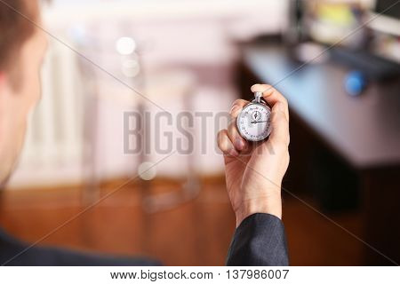 Man holds stopwatch in hand, close up