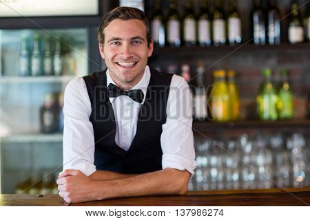 Portrait of happy bartender leaning on bar counter
