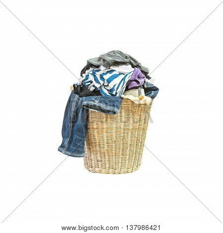 Closeup wood weave basket for used clothes with pile of clothes in house isolated on white background