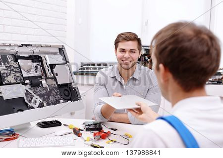 Young man giving broken laptop to repairer in service center