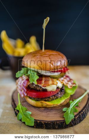 Tasty street food grilled beef burger in crispy shortbread with lettuce and mayonnaise served on small cutting board a rustic wooden table with french fries