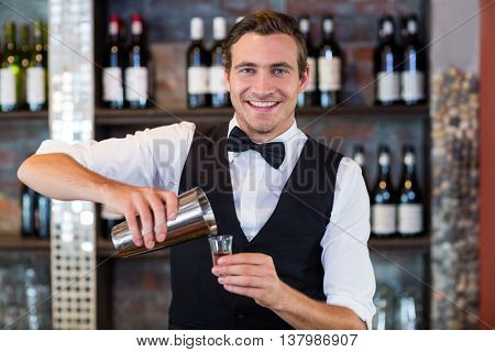 Portrait of bartender pouring tequila into shot glass at bar counter in bar