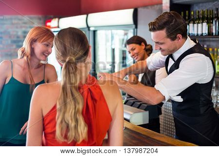 Friends standing at counter while bartender preparing a drink in bar